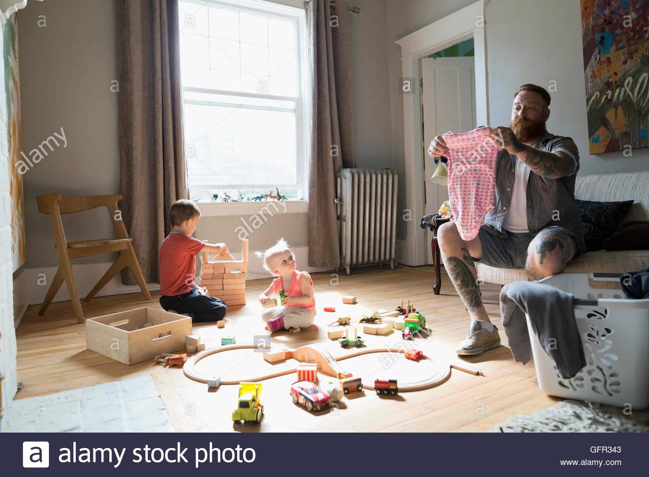 Vater, die Falten von Wäsche in der Nähe von Kinder spielen mit Spielzeugeisenbahn und Holzpflaster Stockbild