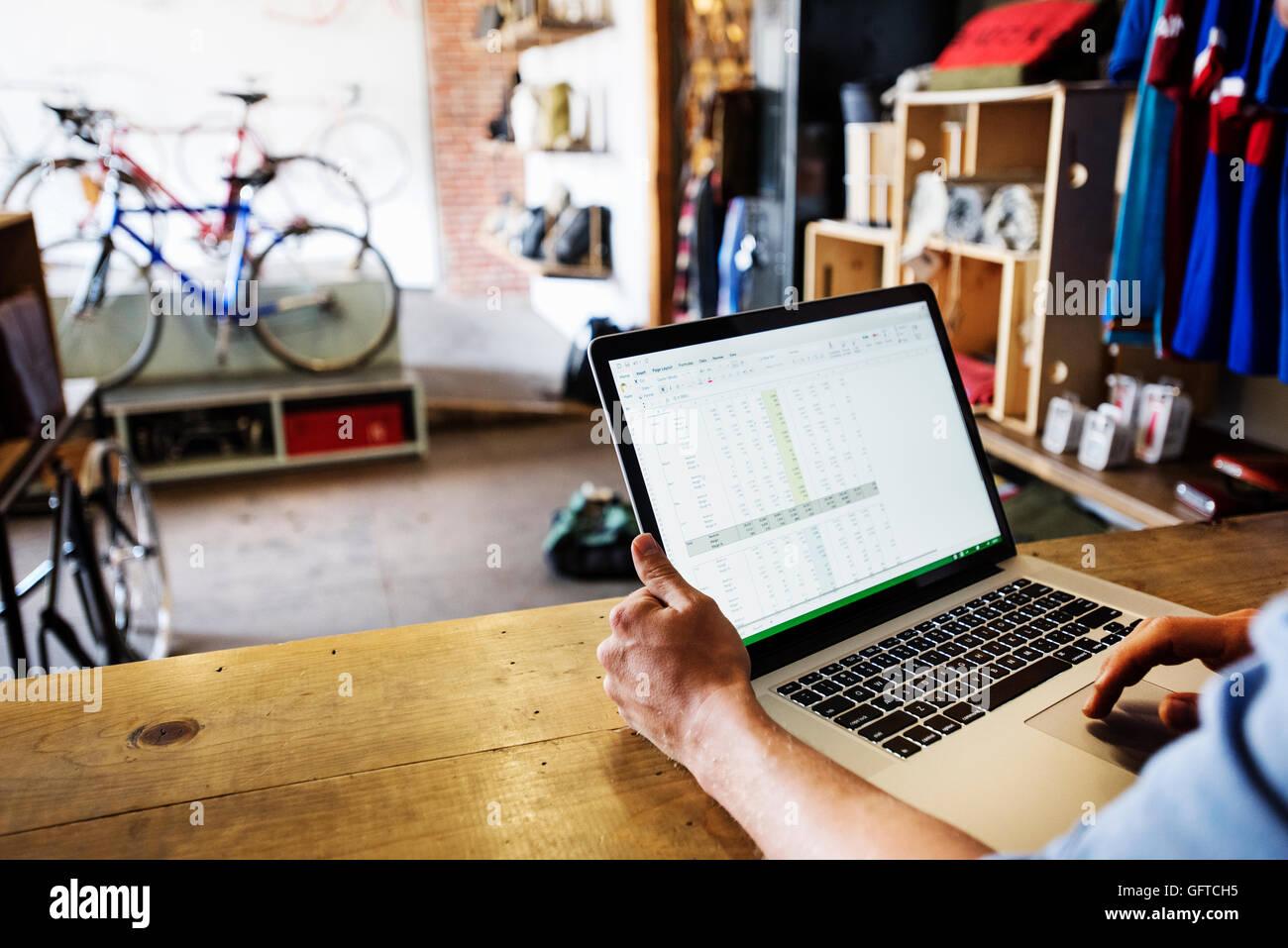 Ein Mann in eine Fahrradwerkstatt mit einem Laptop-Computer, die Führung eines Unternehmens Stockbild