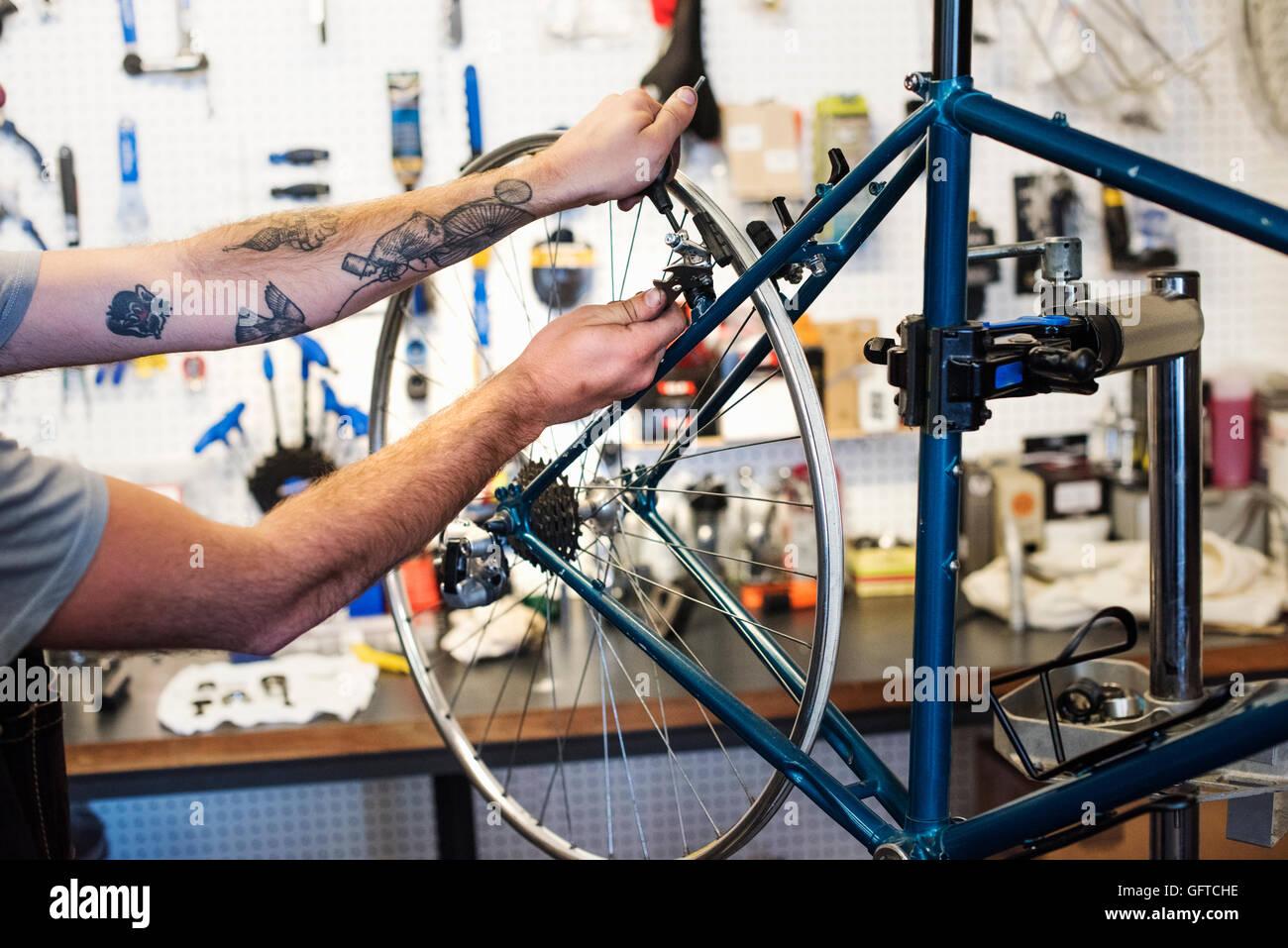 Ein Mann, der arbeitet in einer Fahrradwerkstatt Stockbild
