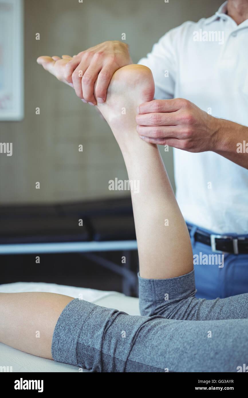 Frau empfangende Fußmassage von Physiotherapeuten Stockbild