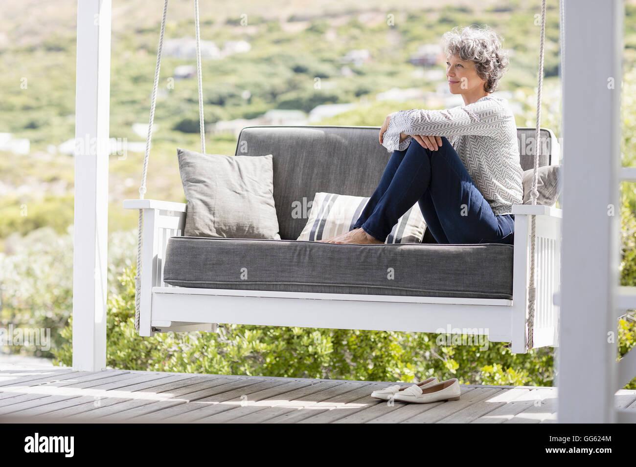 Reife Frau sitzen auf einer Schaukel auf einer Veranda Stockbild