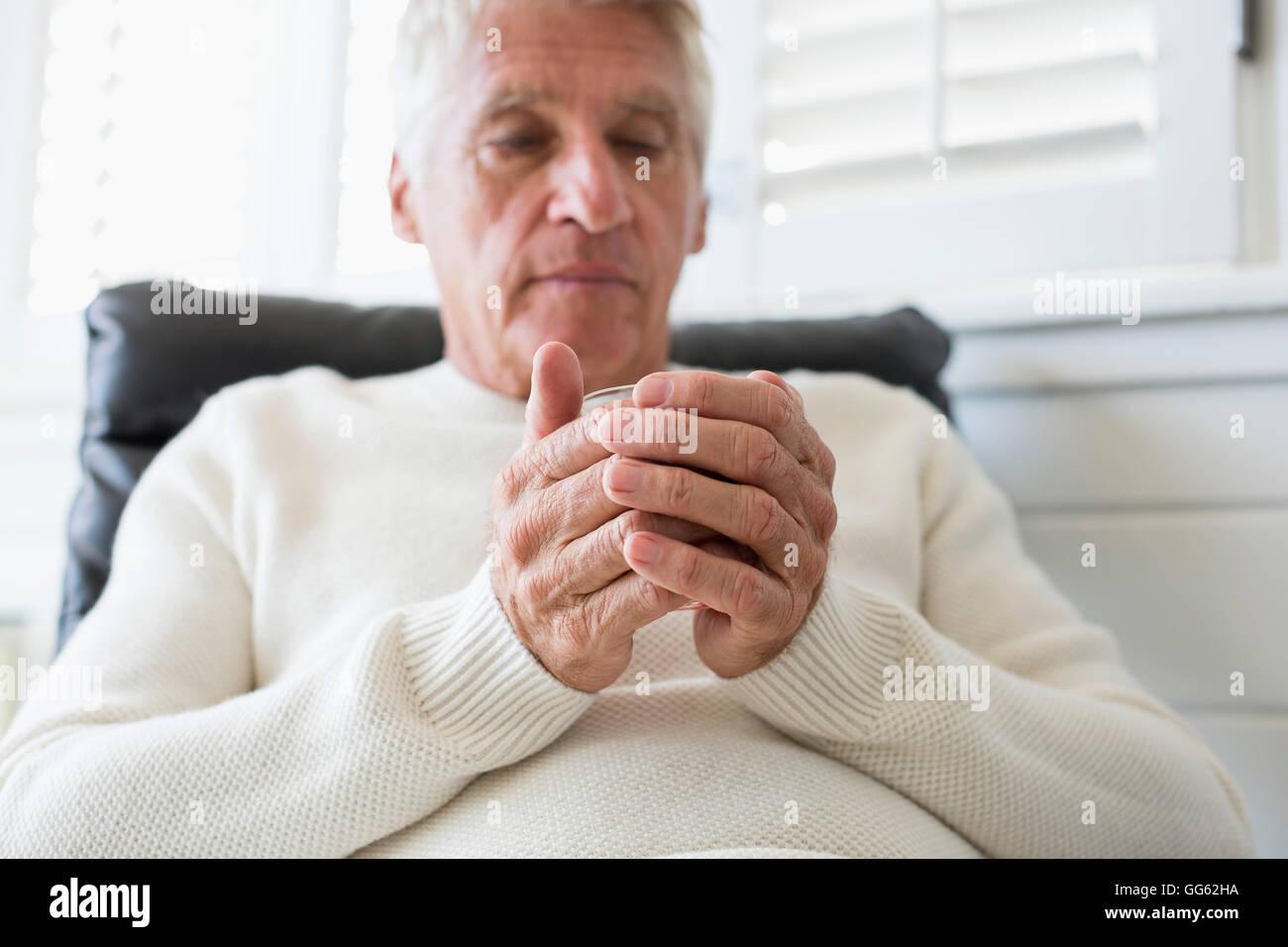 Ältere Mann hält eine Tasse Tee Stockbild