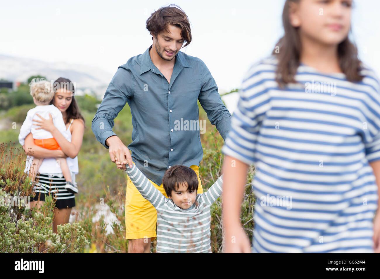 Familie gehen auf einer Wiese Stockbild