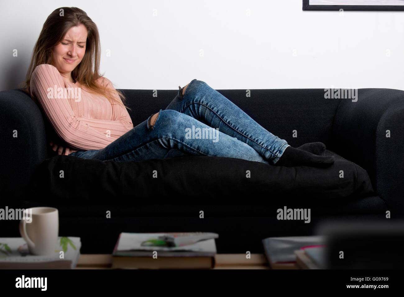 Frau liegend auf einer Couch mit Schmerzen im Bauch Stockbild