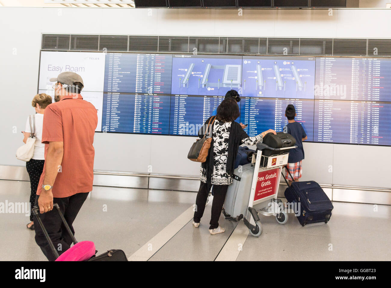 Toronto Pearson International Airport - Passagier-Familie betrachten Anzeigentafel im Terminal 1 Stockfoto