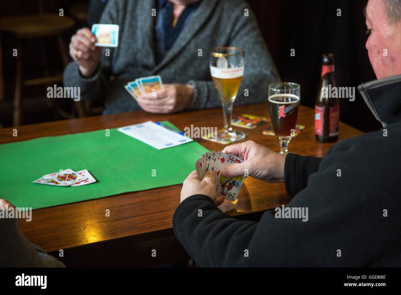 Ältere Karten Spieler Spielkarten auf Tisch im pub Stockbild