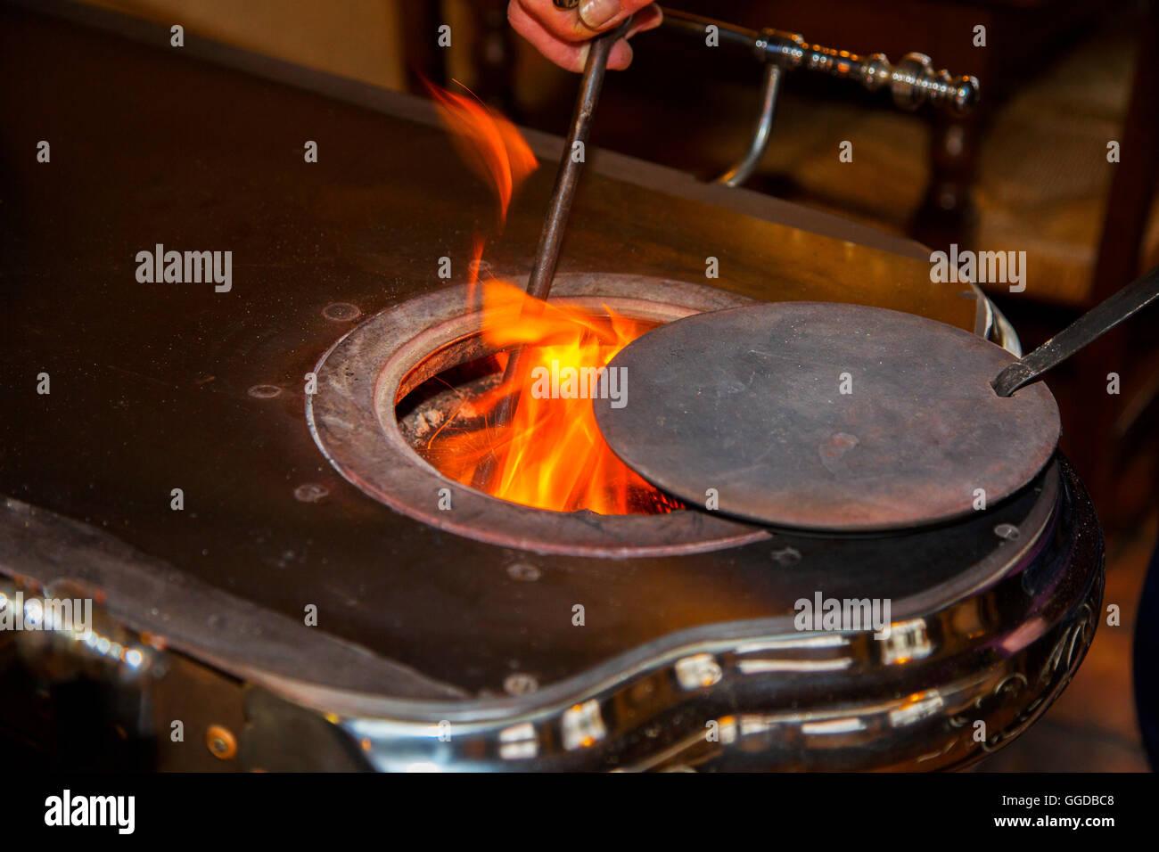 Vintage gusseisernen Kohleofen / Leuvense Stoof, Flammen und Poker Stockbild