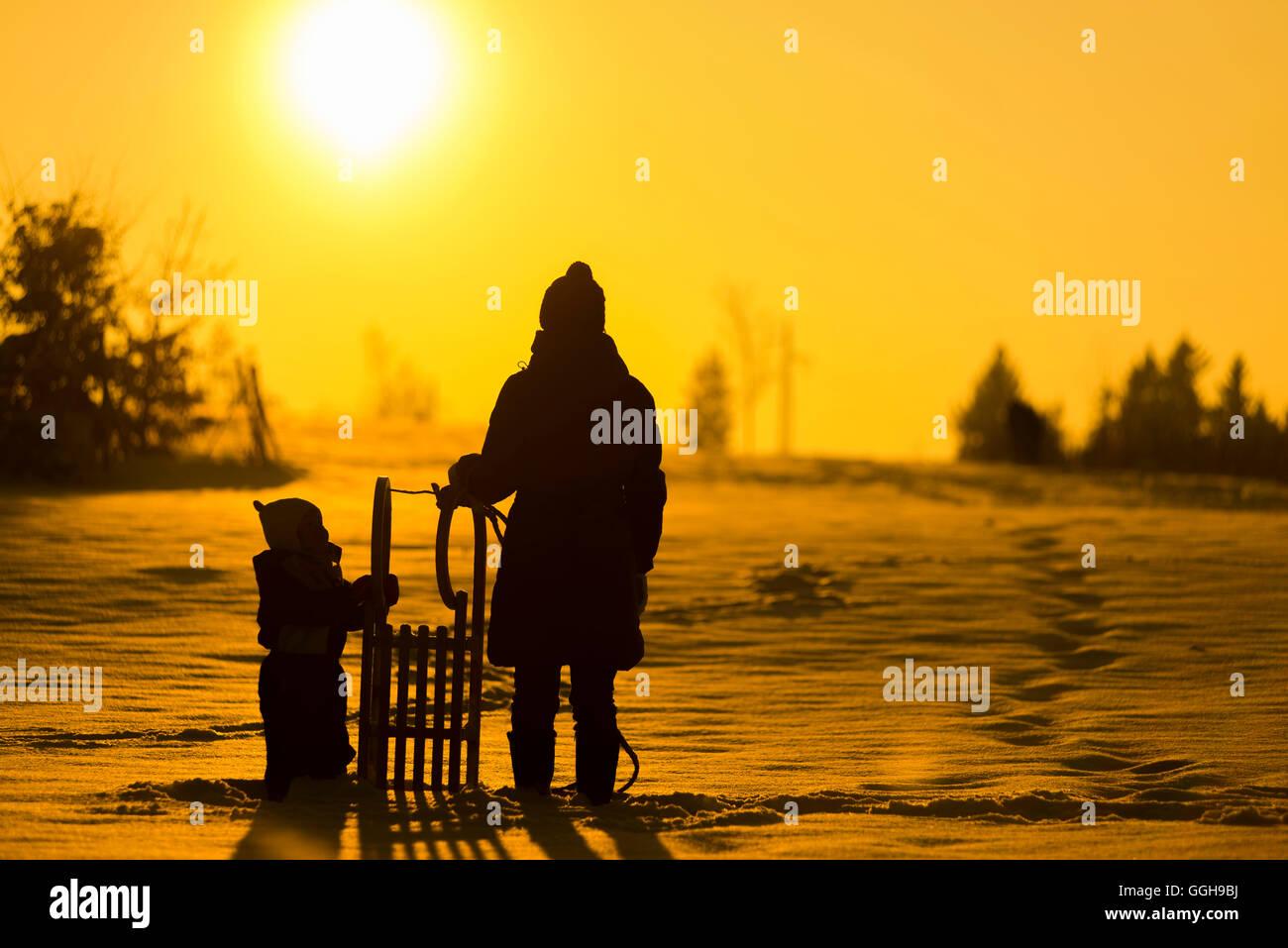Mutter stand mit einem kleinen Kind und Schlitten im Schnee und Blick auf die Winter Sonne, Hintergrundbeleuchtung, Stockbild