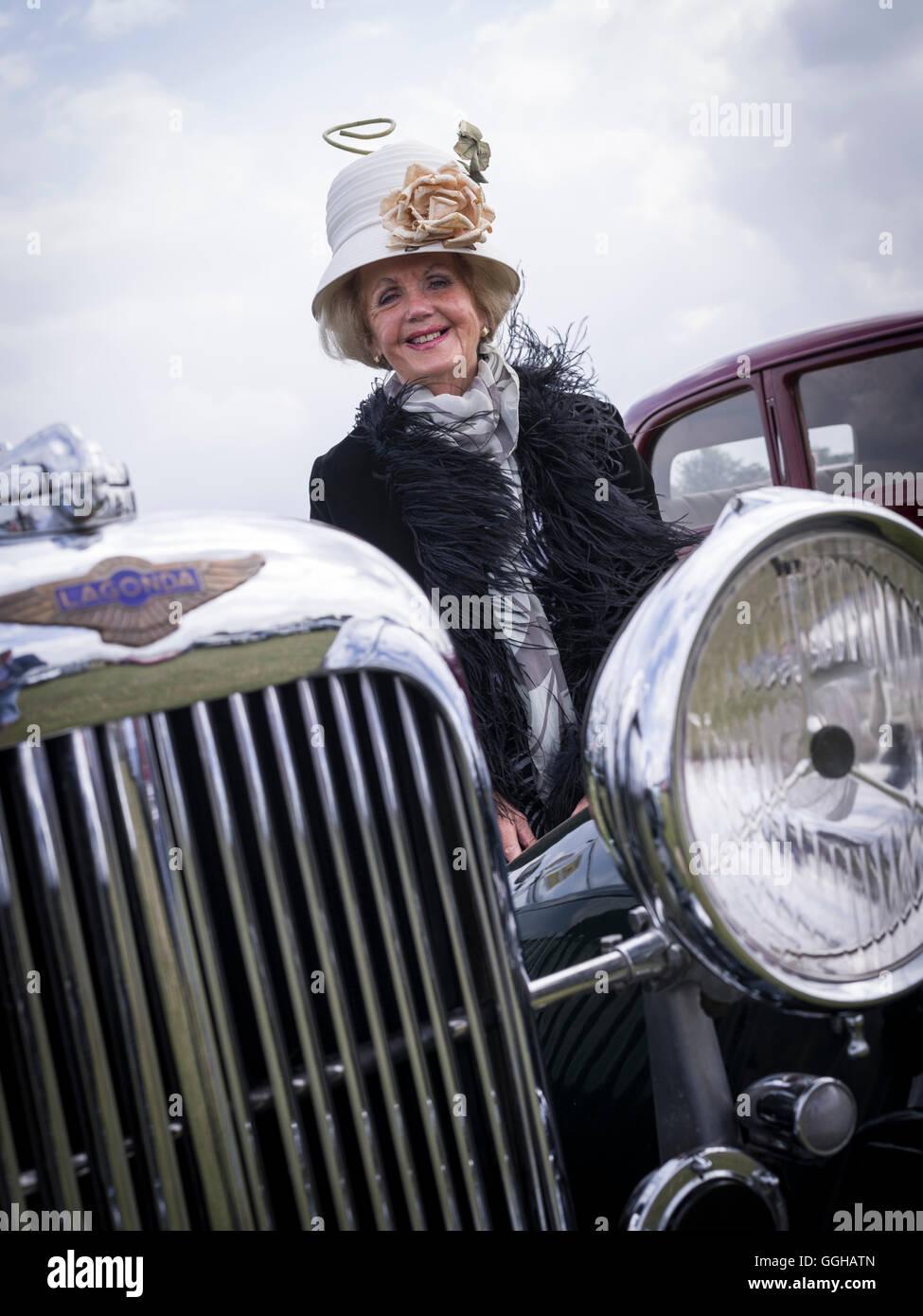 Besucher freut sich über den passenden Hut für ihre Lagonda, Goodwood Revival 2014, Racing Sport, Oldtimer, Stockbild