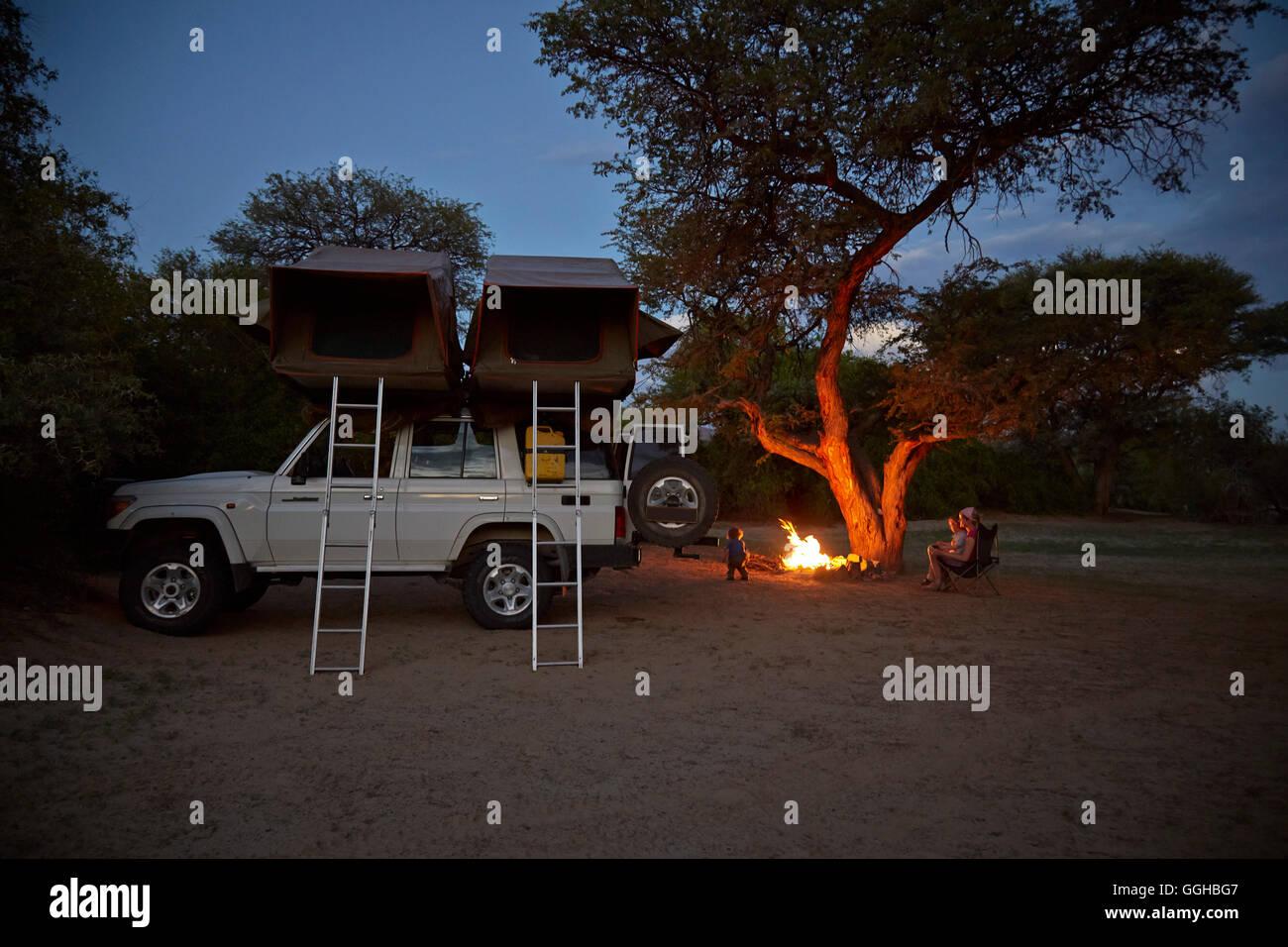Familie um ein Lagerfeuer, Geländewagen mit Dachzelt im Vordergrund, Purros Camp, Hoarusib, Namib-Wüste, Stockbild