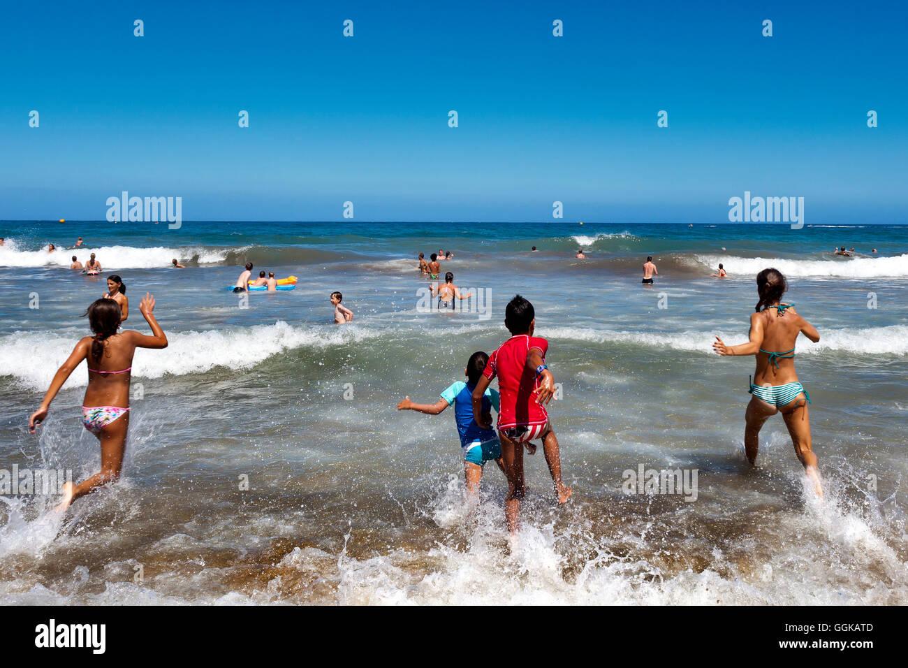 Kinder laufen ins Meer, Playa del Ingles, Gran Canaria, Kanarische Inseln, Spanien Stockbild