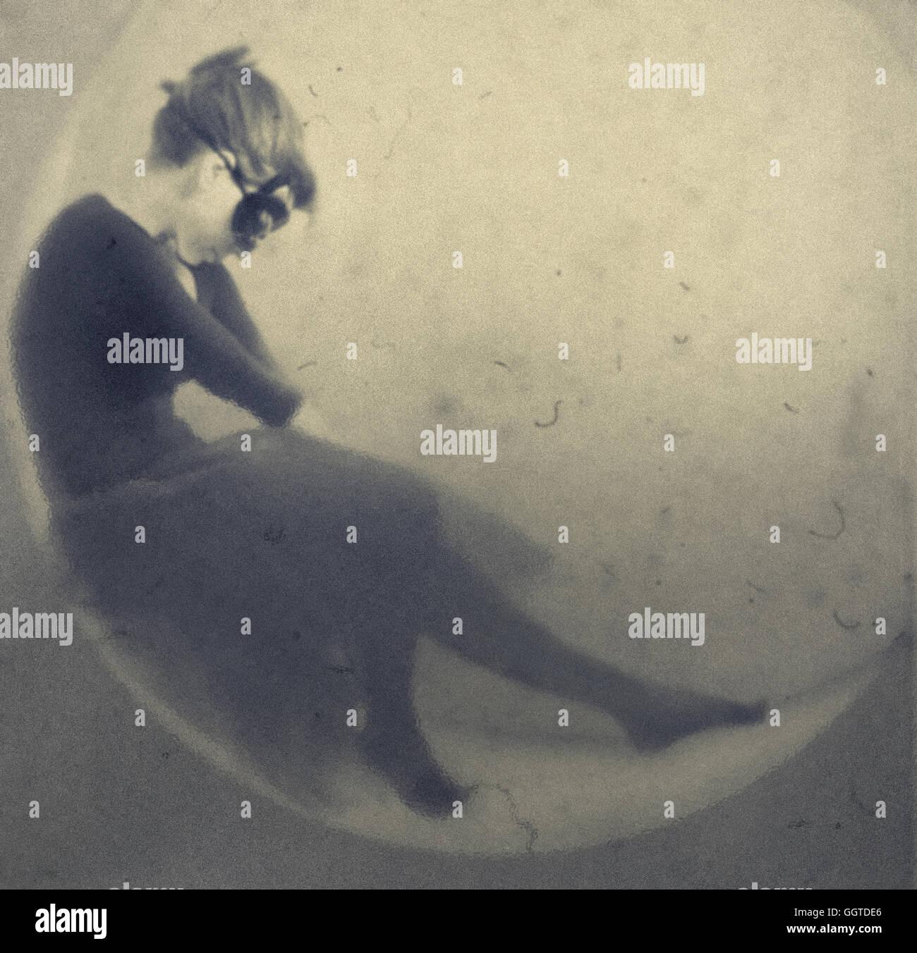 surreale Portrait junge Frau trägt schwarze Gesichtsmaske sitzen auf Mondsichel Stockfoto