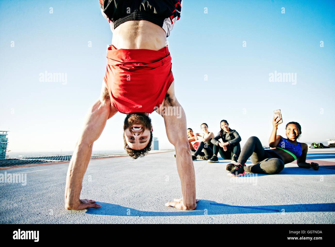 Frau fotografieren Mann tun Handstand auf städtischen Dach Stockfoto