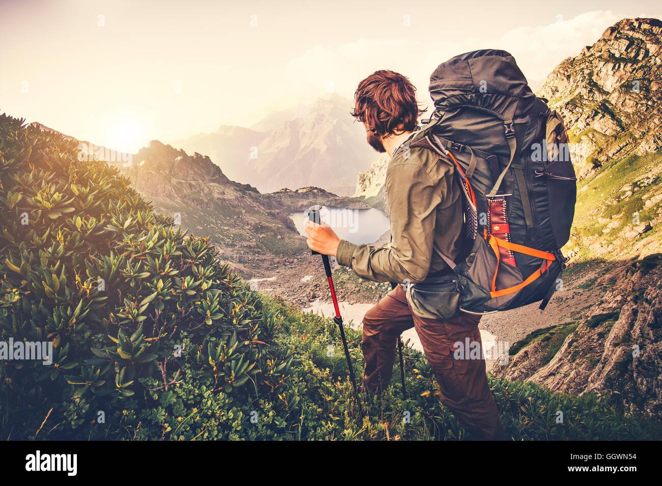 Reisender Mann mit Rucksack Bergsteigen Reisen Lifestyle Konzept See und die Berge im Hintergrund Expedition Sommerferien Stockbild