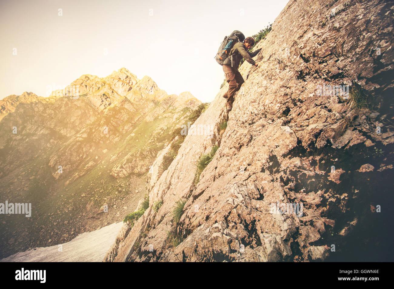 Mann-Reisenden mit großen Rucksack Klettern auf Felsen Reisen Lifestyle Konzept Berge Landschaft im Hintergrund Stockbild