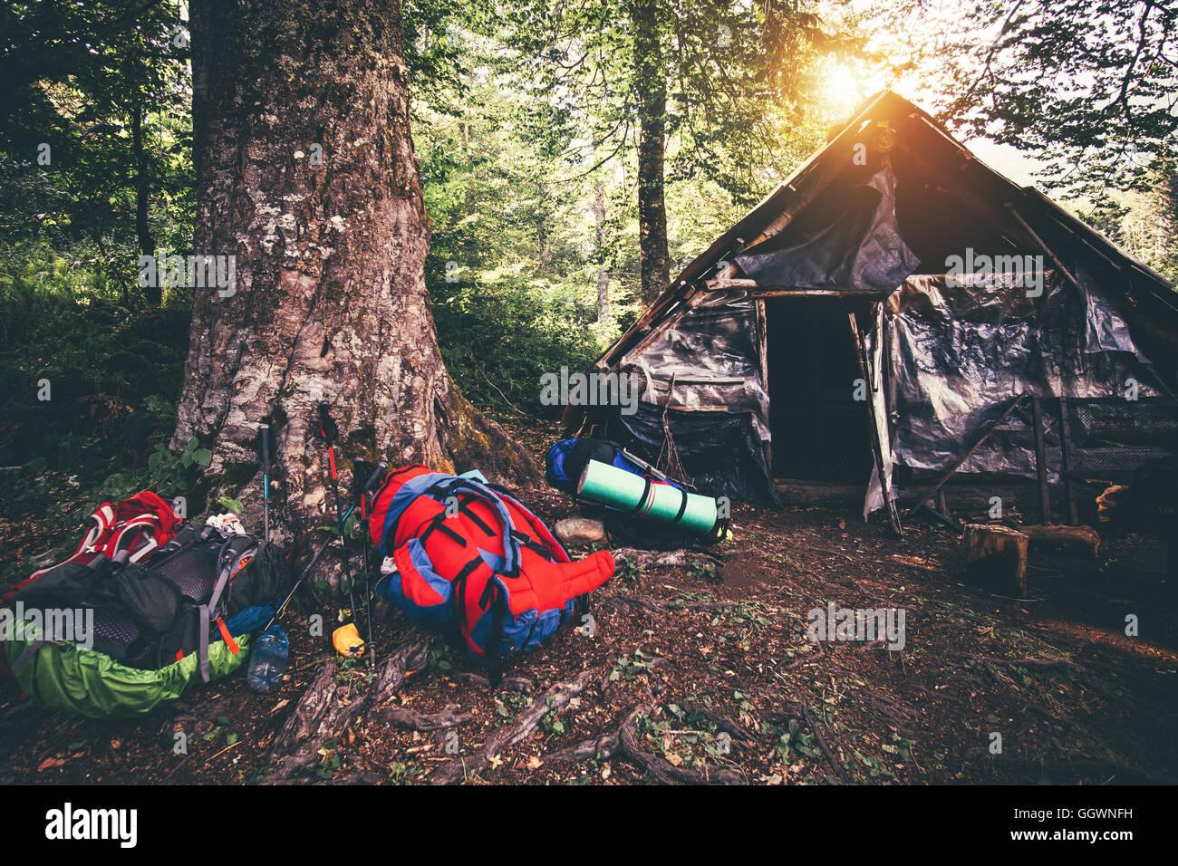 Rucksäcke und verlassenen Haus camping outdoor Travel-Lifestyle Wanderausrüstung Wald Natur auf Hintergrund Stockbild