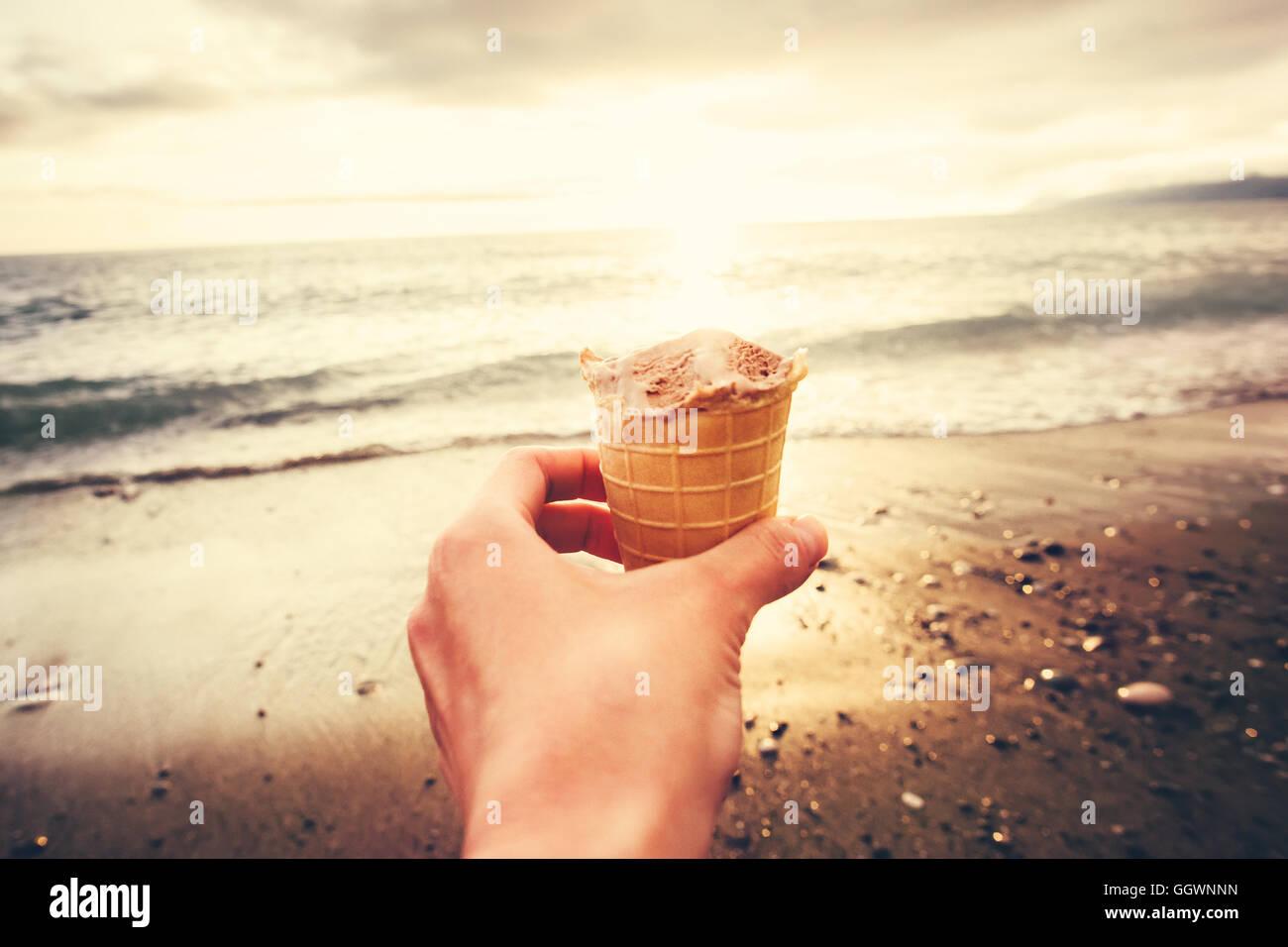 Hand mit Eis mit Meer Strand Sonnenuntergang auf Hintergrund-Sommer-Urlaub-Reisen-Lifestyle-Konzept Stockbild