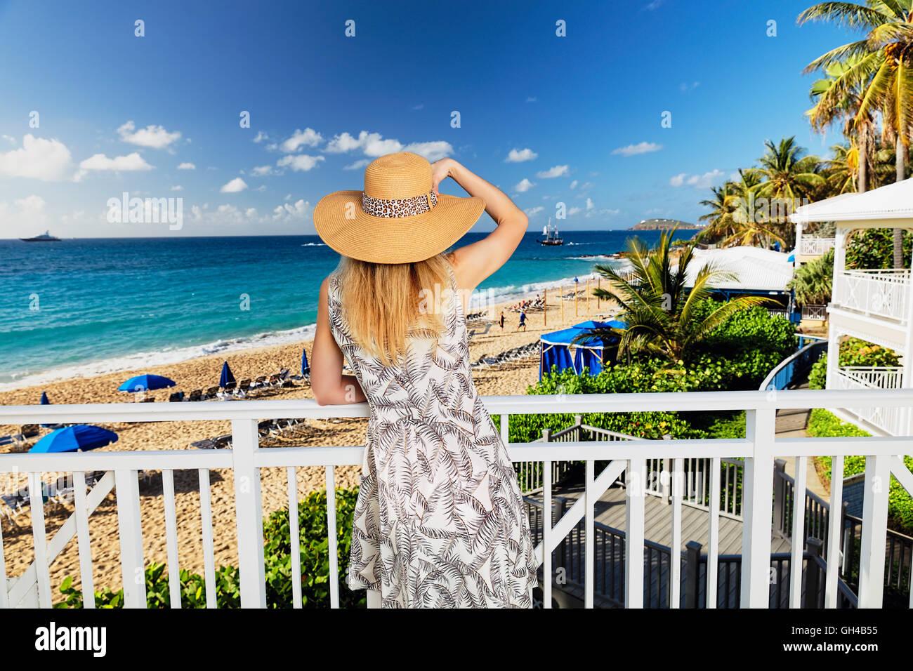 Rückseite Blick auf eine Frau in einem Sommerkleid und Hut ein Beach Resort von einem Balkon aus auf Stockbild