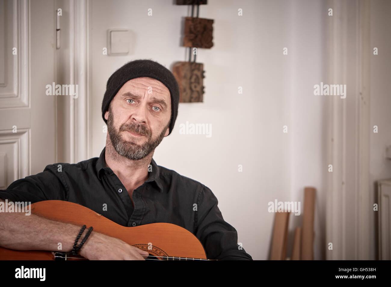 Alte Hiptser mit Bart und Hut hält eine Gitarre zu Hause sitzen vor der Tür Stockbild
