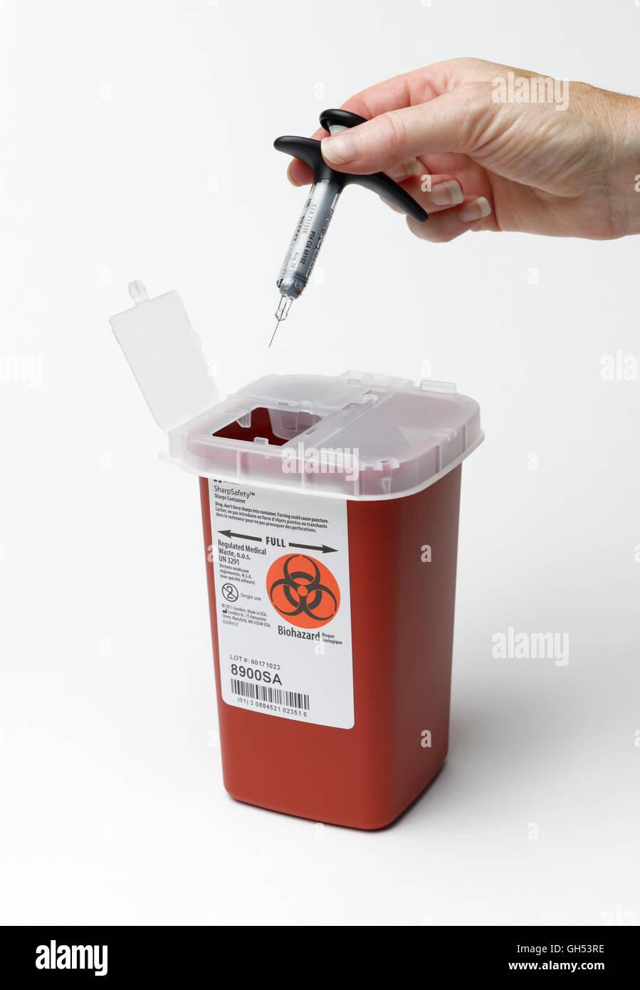 Eine Spritze in eine Sharps Container für medizinische Abfälle entsorgen, nach einer Injektion von Medizin Stockfoto