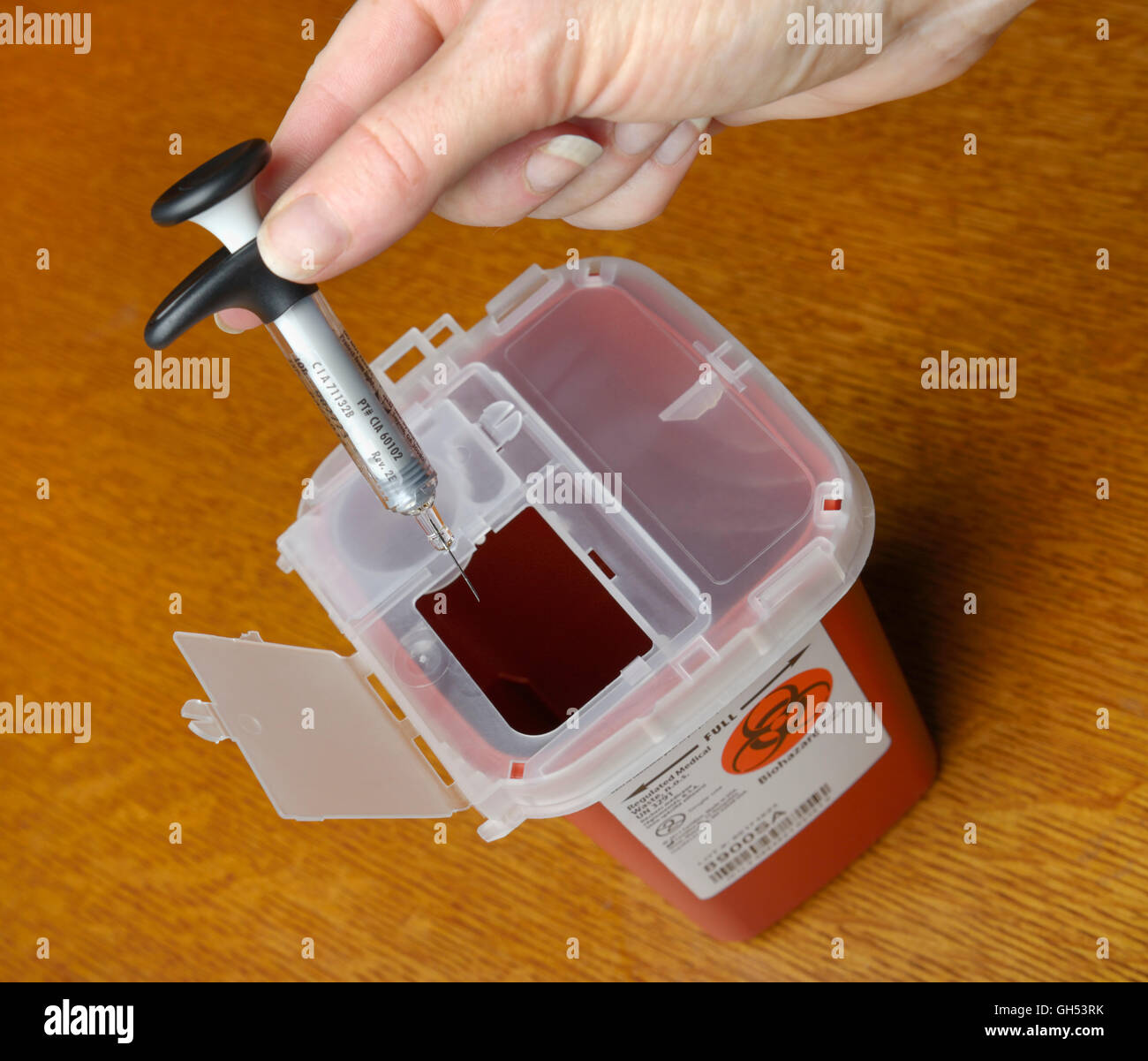 Eine Spritze in eine Sharps Container für medizinische Abfälle entsorgen, nach einer Injektion von Medizin Stockbild