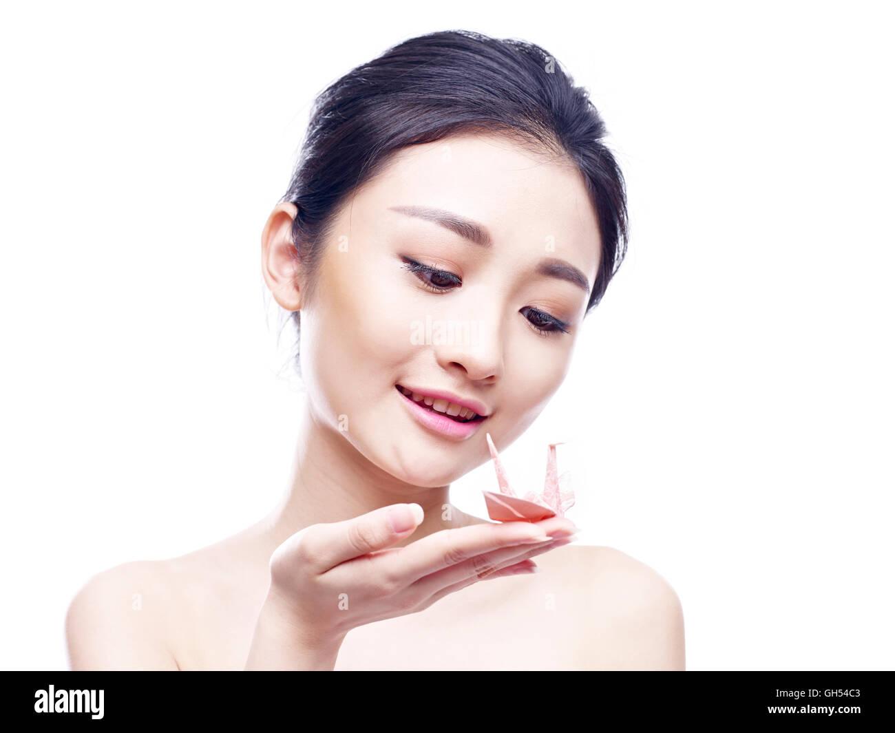junge asiatische Frau halten und mit Blick auf einen Papierkranich isoliert auf weißem Hintergrund. Stockbild