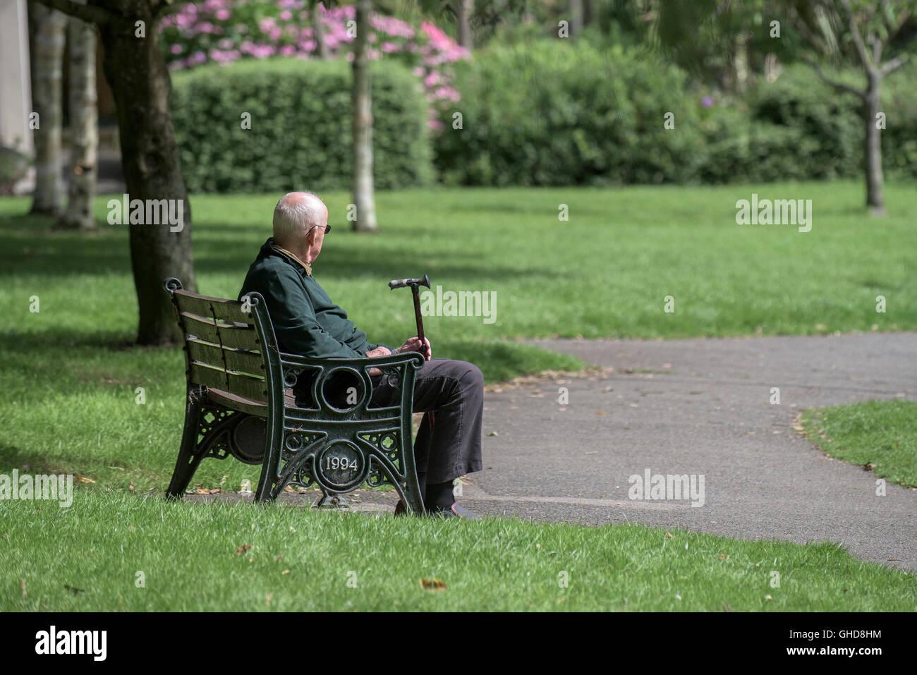 Ein älterer Mann sitzt allein in Trenance Gärten in Newquay, Cornwall. Stockbild