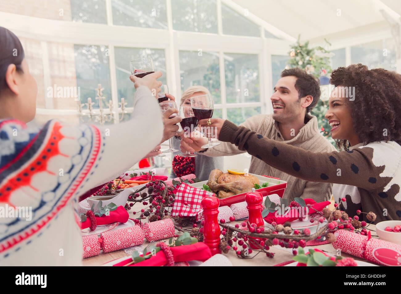 Freunde, toasten Weingläser am Weihnachtstisch Stockfoto