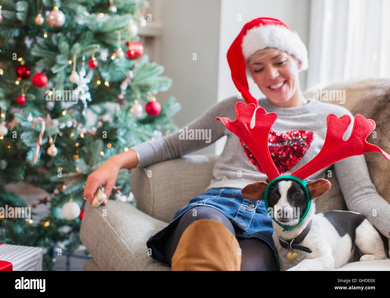 Frau mit Hund trägt Rentier-Geweih Weihnachtsbaum auf Sofa sitzen ...