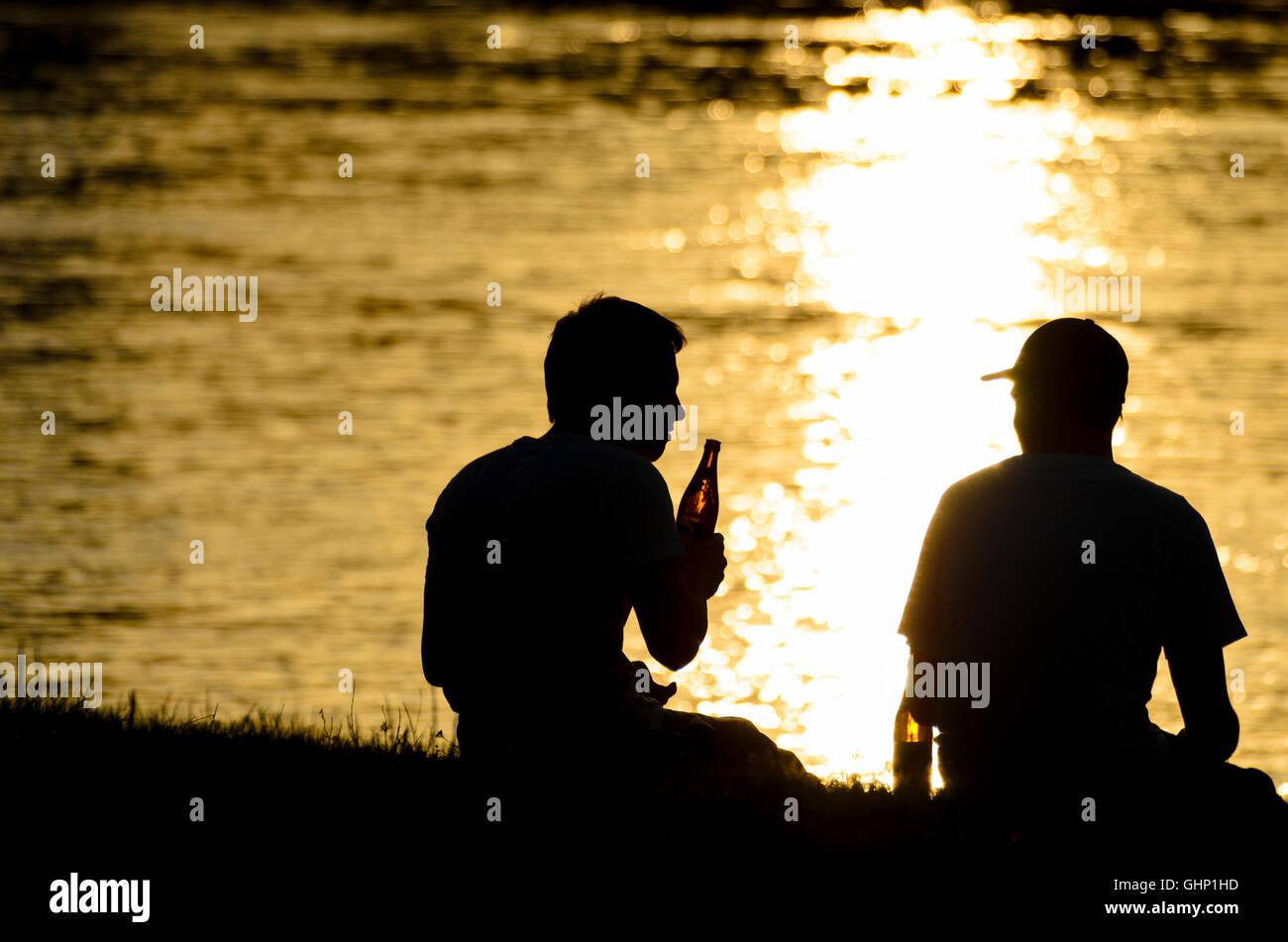 2 junge Teenager Teenager Biertrinker entlang der Donau, untergehende Sonne, Österreich, Stockbild