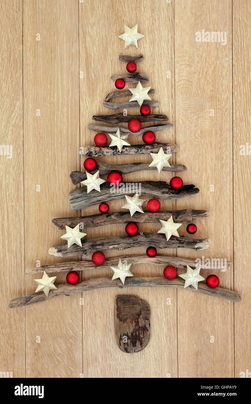 Treibholz-Weihnachtsbaum mit Stern und Rote Christbaumkugel Dekorationen  über Eiche Holz Hintergrund.