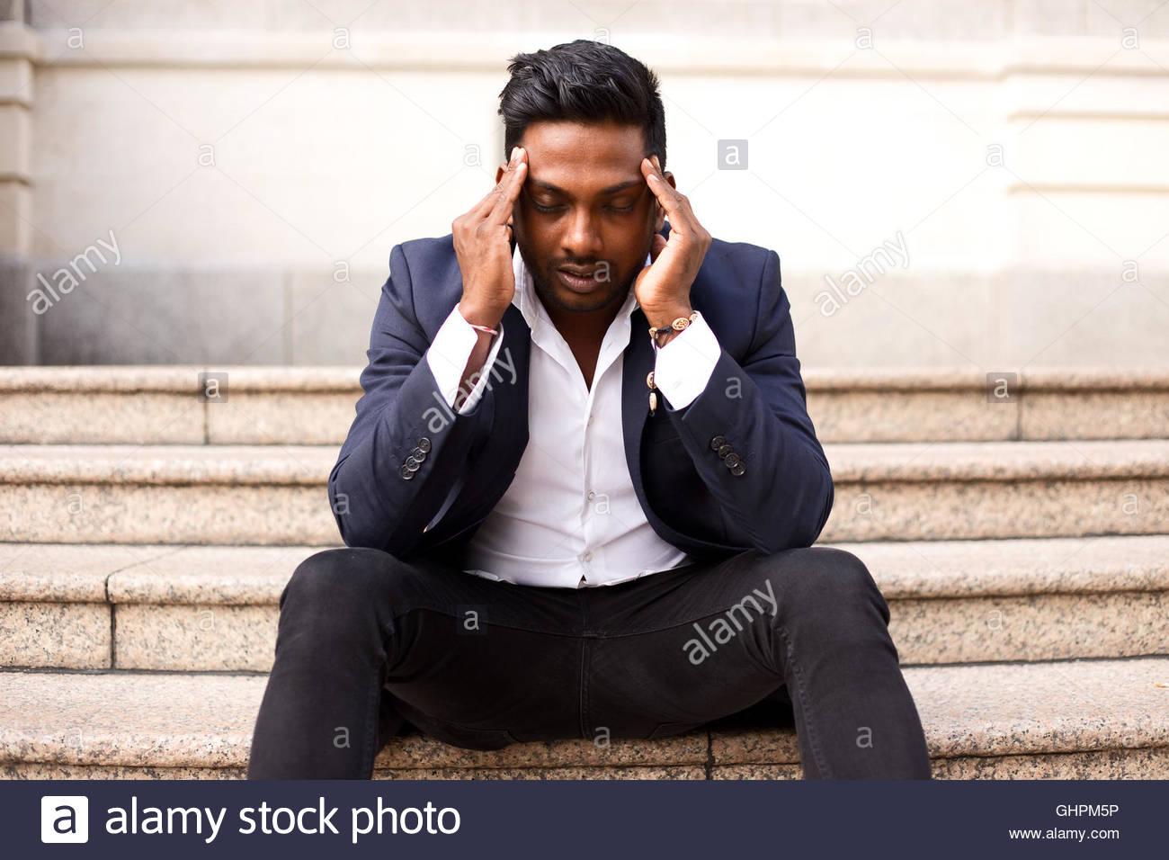 Geschäftsmann, sitzen auf einer Stufe mit Kopfschmerzen Stockbild