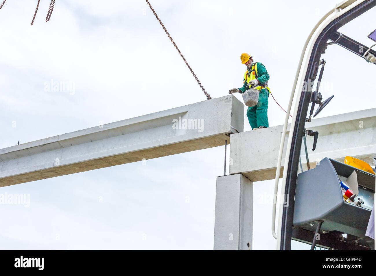 Höhe-Arbeiter ist hoch oben auf Betonrahmen ohne ordnungsgemäße ...