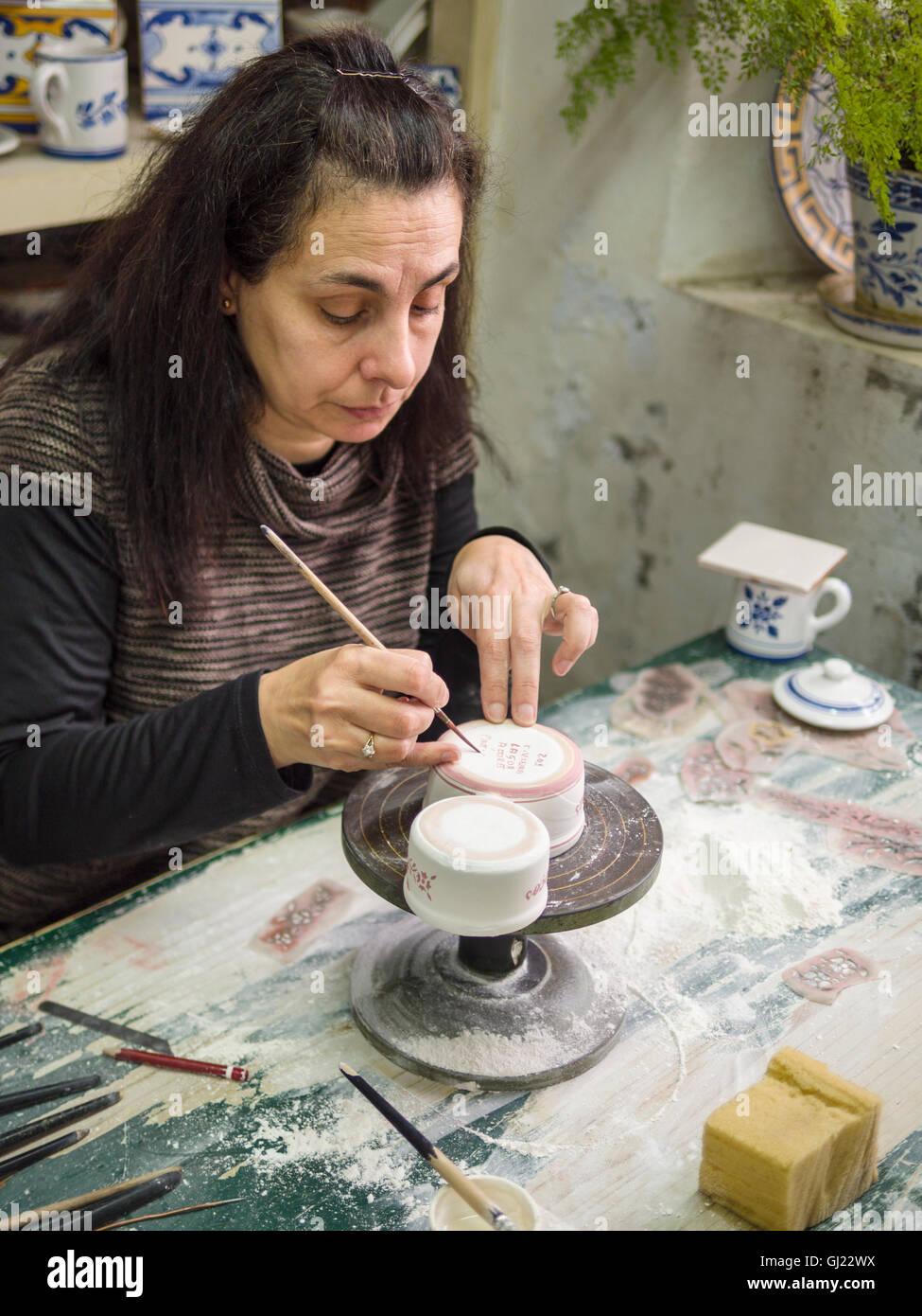 Eine abschließende Unterschrift auf einer Keramik-Tasse. Eine Arbeitnehmerin malt eine Unterschrift auf einem Stockbild