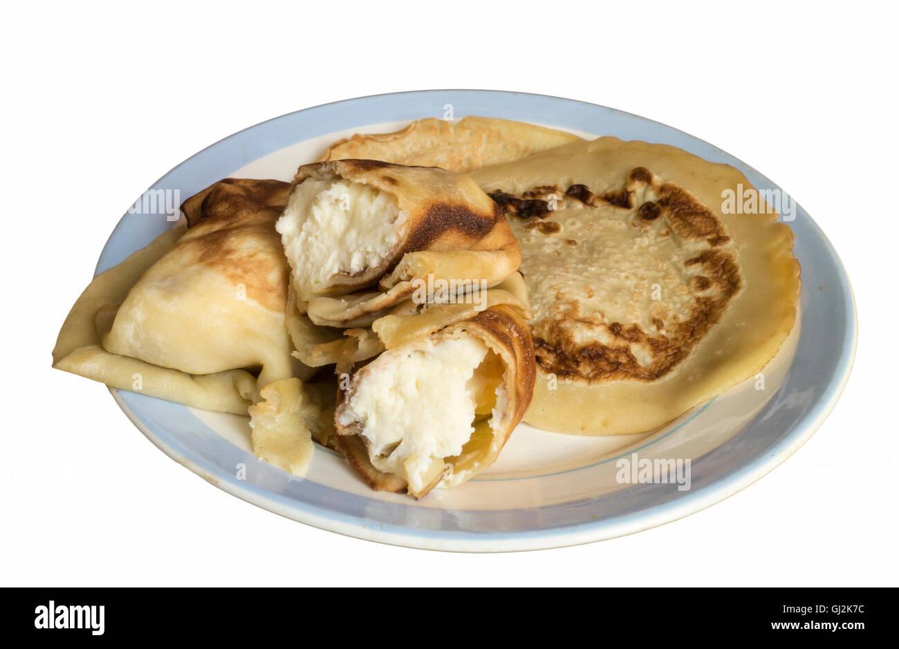Nach Hause Pfannkuchen mit weißen Topfen für Morgenmahlzeit ist auf der blauen Platte isoliert Stockbild