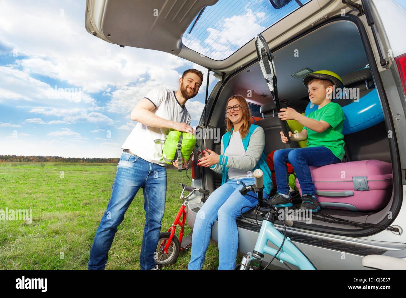 Junge Familie laden Kofferraum für die Autofahrt Stockbild