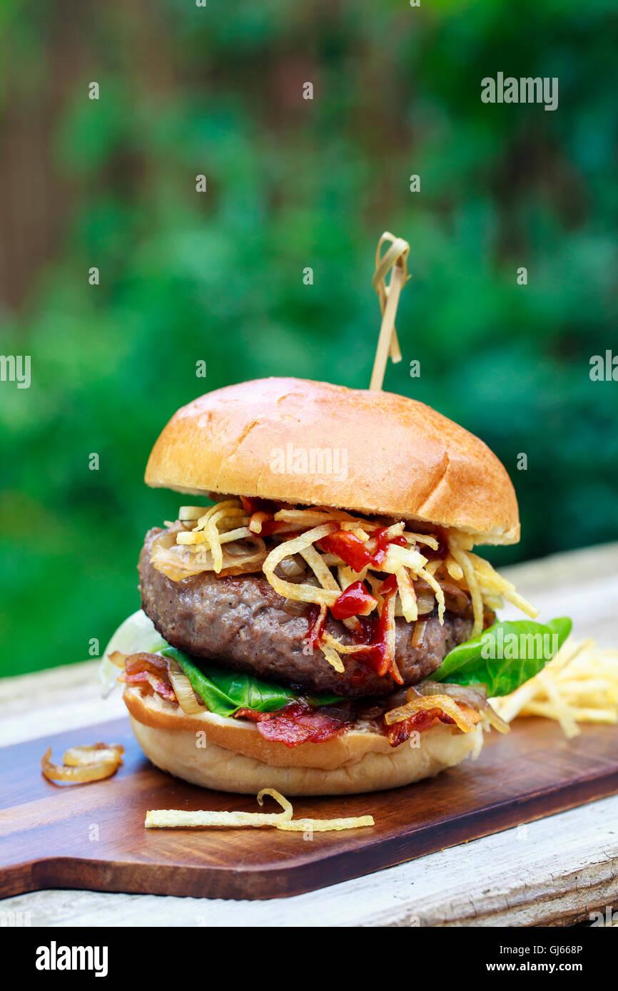 Beefburger mit gebratenen Zwiebeln, Speck und Zeichenfolge Pommes in Brioche Brötchen Stockbild