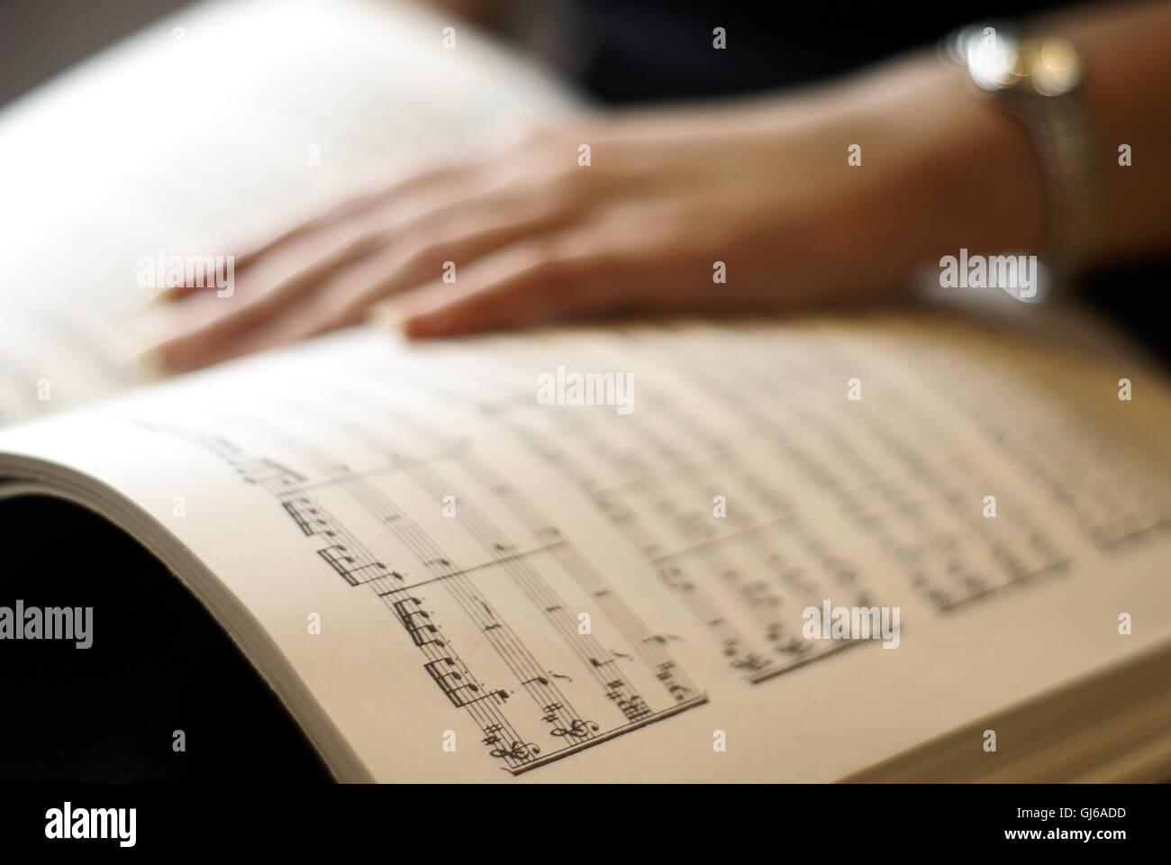 Weibliche Hand auf Partitur buchen Seite Stockbild