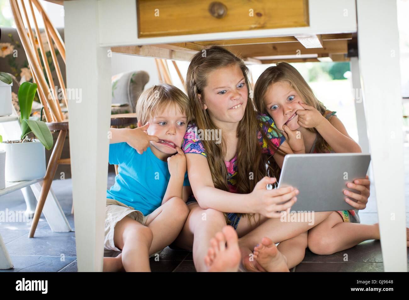 EIGENTUM FREIGEGEBEN. -MODELL VERÖFFENTLICHT. Drei Geschwister unter Tisch mit digital-Tablette. Stockbild