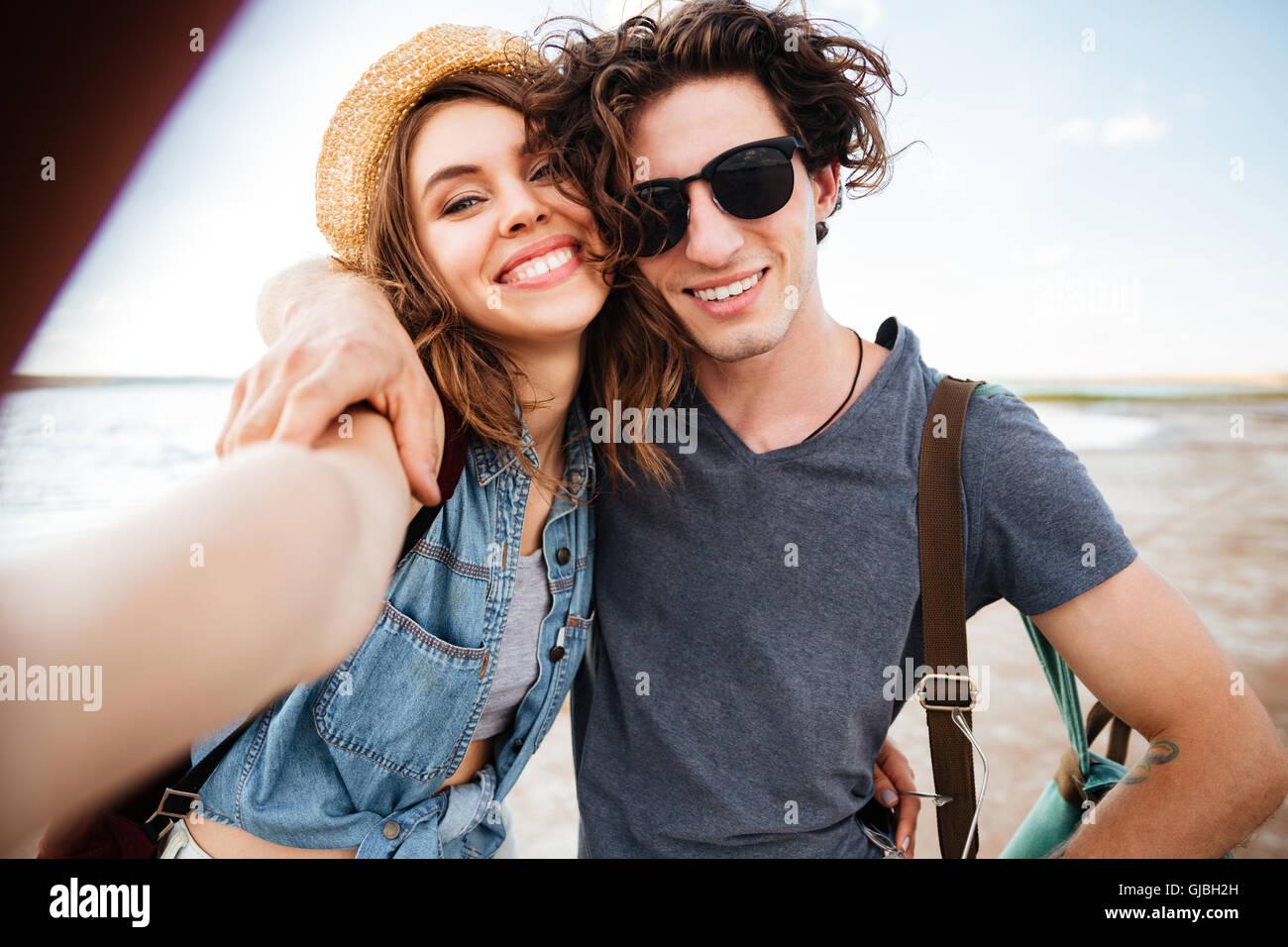Lächelnde schöne junge Paar umarmt und nehmen Selfie am Strand Stockbild