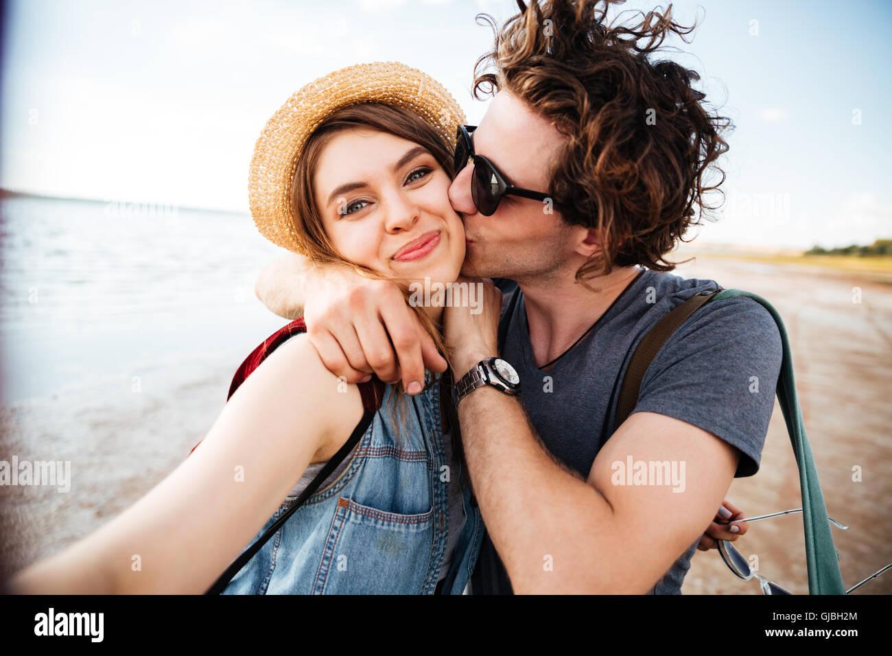 Glückliches junges Paar küssen und unter Selfie im freien Stockbild