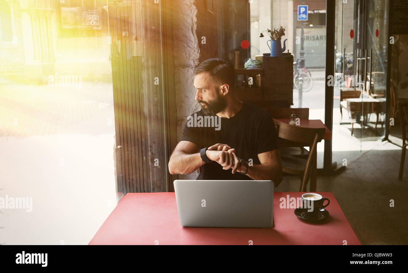 Junge bärtige Geschäftsmann tragen schwarze Tshirt arbeiten Laptop Urban Cafe.Man sitzen Holztisch Tasse Stockbild