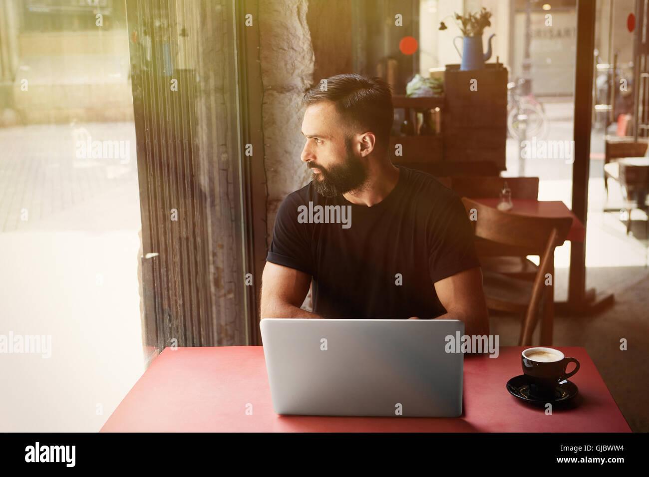 Young bärtigen Geschäftsmann tragen schwarz Tshirt arbeiten Laptop Urban Cafe.Man sitzen Holz Tisch Tasse Stockbild
