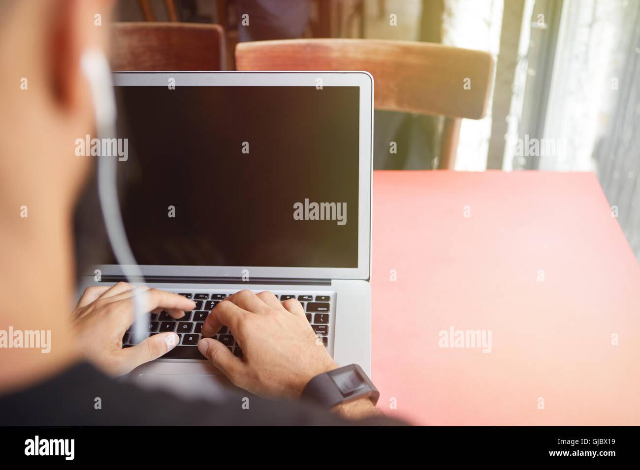 Junge bärtige Geschäftsmann tragen schwarze Tshirt arbeiten Laptop Urban Cafe.Man sitzen Holztisch Kopfhörer Stockbild