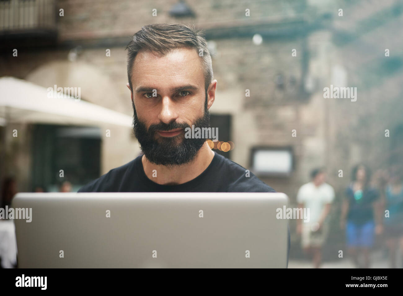 Closeup Portrait schöne bärtige Geschäftsmann tragen schwarze Tshirt arbeiten Laptop Urban Cafe.Young Stockbild