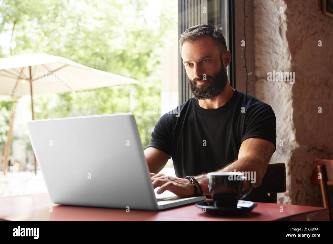 Gut aussehend bärtigen Geschäftsmann tragen schwarze Tshirt Laptop Holztisch Urban Cafe.Young Manager Stockbild