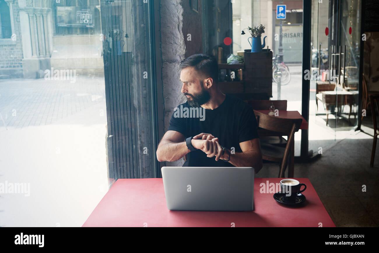 Junge bärtige Geschäftsmann tragen schwarze Tshirt Urban Cafe.Man Laptop sitzen Holztisch Tasse Kaffee Stockbild