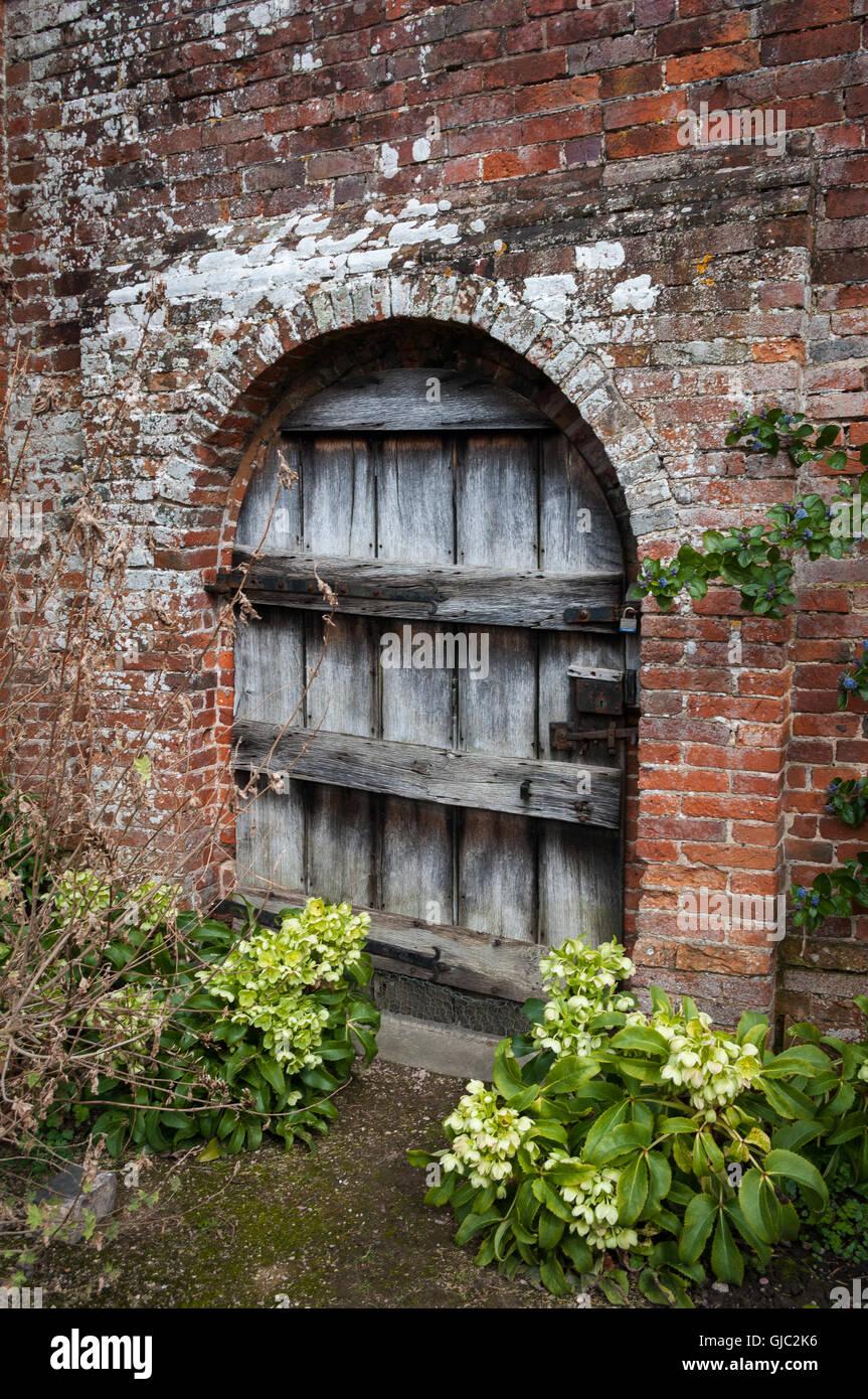 Alte Garten Tür Von Verwittertem Holz Im Torbogen In Mauer.