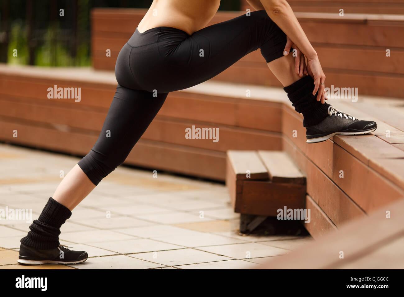 Fitness-Frau, die Beine vor dem Training im freien Stockbild