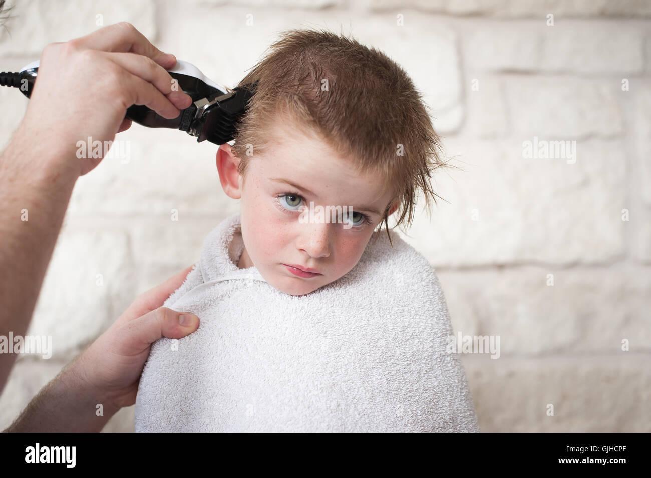 Junge, eine Summen Haare schneiden von seinem Vater Stockfoto